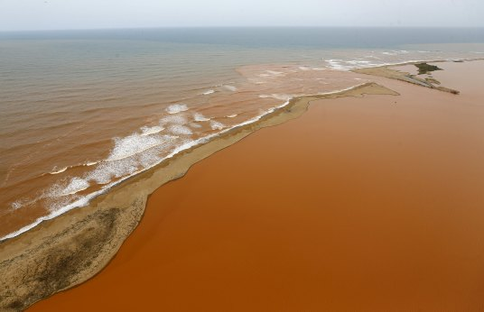An aerial view of the Rio Doce (Doce River), (bottom) which was flooded with mud after a dam owned by Vale SA and BHP Billiton Ltd burst, at an area where the river joins the sea (top) on the coast of Espirito Santo in Regencia Village, Brazil, November 23, 2015. REUTERS/Ricardo Moraes